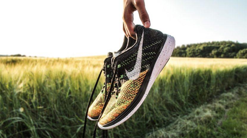 baskets tenue en main avec le logo swoosh Nike